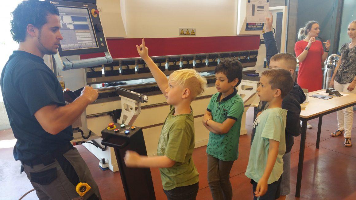 De kinderen van de lagere school helpen mee aan de machine in de technische school