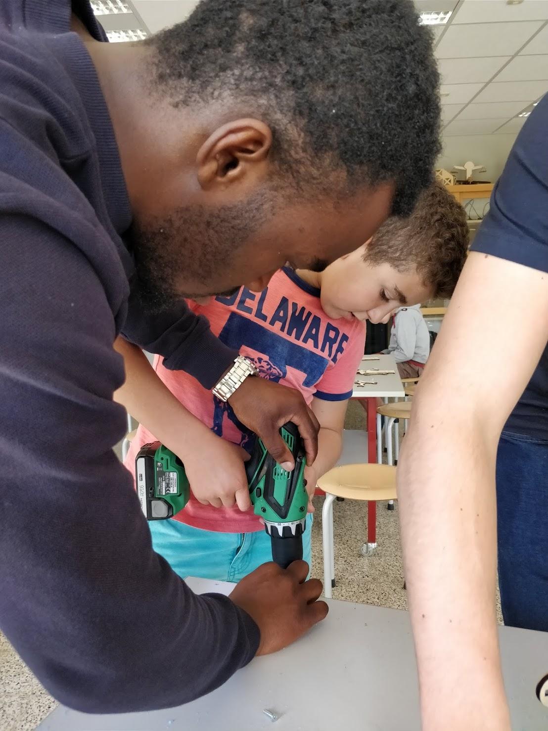 Leerlingen van de lagere school helpen mee in de technische school.